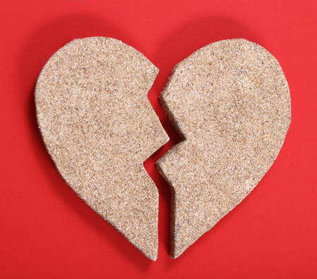heartbreaking: Broken heart from sand on the red background