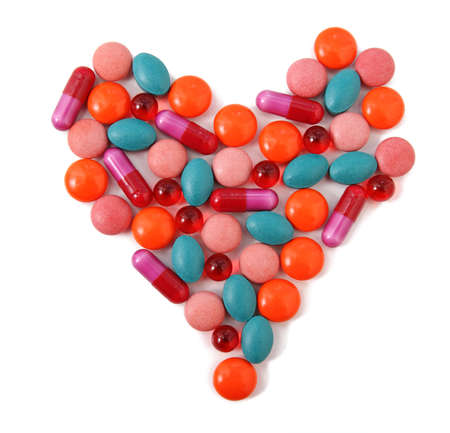 antibiotic pink pill: Heart from milticolor pills on white background Stock Photo