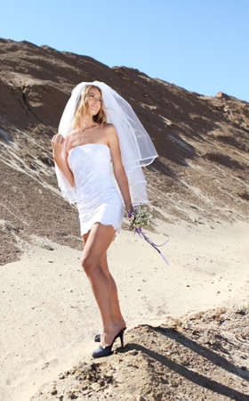 Beautiful bride in her white dress on a windy summer day photo