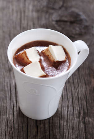 Mug of hot chocolate or cocoa with marshmallows on the wooden background photo