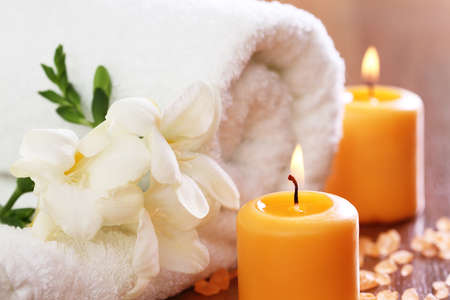 Spa setting with freesia, towel, burning candles and salt  photo
