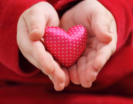 pink satin: Childs hands hold heart from a pink satin with pattern