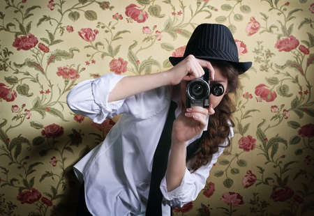 Portrait of the beautiful stylish brunette woman with old camera photo