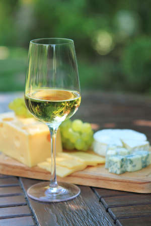 white wine glass: Various sorts of cheese, grapes and one glass of the white wine