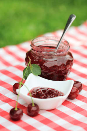 Jar of cherry jam and some cherries on the napkin photo