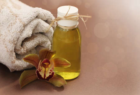 oil massage: Spa setting with orchid, towel and massage oil Stock Photo