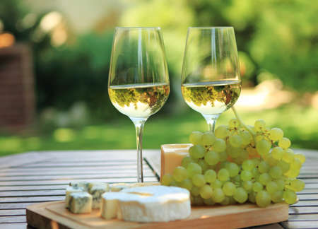 vino: Varios tipos de queso, uvas y dos vasos de vino blanco
