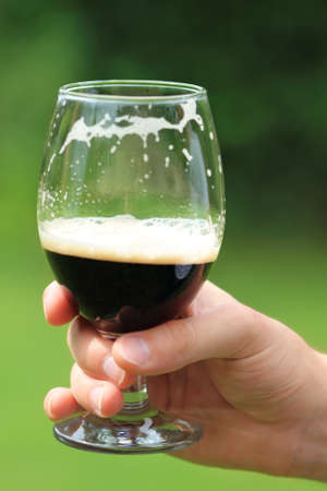 Man with one  beer glass with dark beer photo