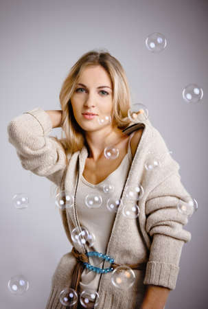 Smiling beautiful blond girl and soap bubbles photo