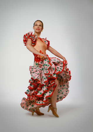 Young woman dancing flamenco with castanets on gray background photo