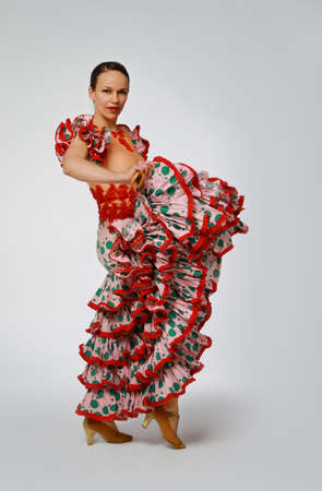 Young woman dancing flamenco with castanets on gray photo