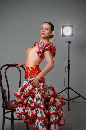 Young woman near the chair dancing flamenco on grey background photo