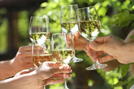 Celebración. Personas que tienen vasos de vino blanco haciendo un brindis. DOF superficial.