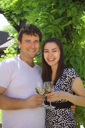 Happy woman and man holding glasses of white wine making a toast Stock Photo - 9685556
