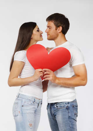 Portrait of a young couple with red heart photo