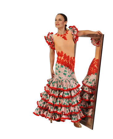 Young woman dancing flamenco near the mirror on white background photo
