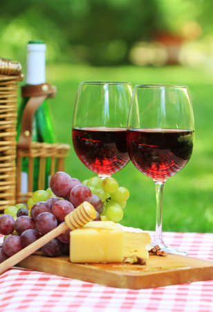 Various sorts of cheese, grapes and two glasses of the red wine photo