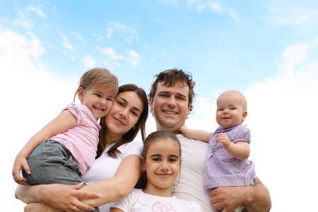 Happy young family with three daughters outdoors photo