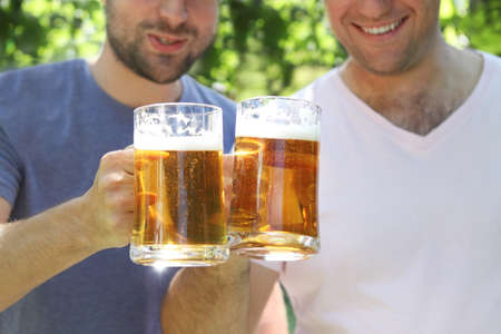 Two men with glasses of the light beer in the garden photo