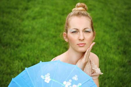 Beautiful blond girl with geisha make up outdoors photo