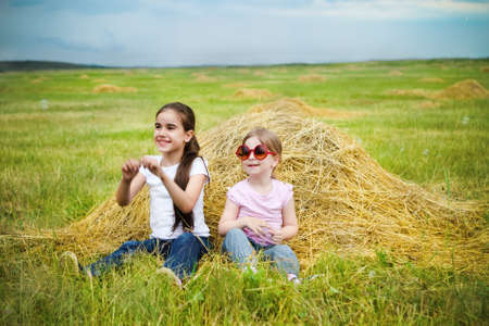 Two happy little sisters having fun in the summer day in field photo