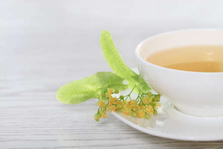 Cup of the linden tea on white wooden background photo
