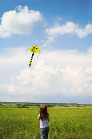 Little girl with flying a kite in the summer field Stock Photo - 9883681