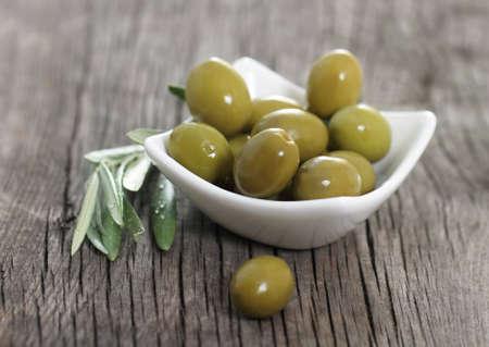 hoja de olivo: Aceitunas verdes en el bowl y la rama de olivo a la mesa de madera Foto de archivo