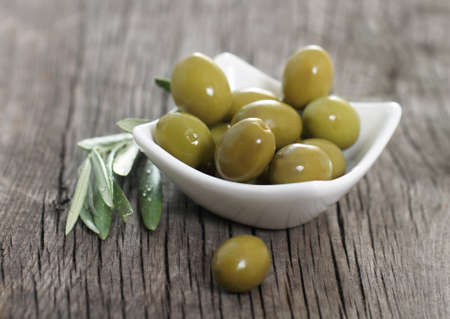 Green olives in the bowl and olive branch on wooden table photo