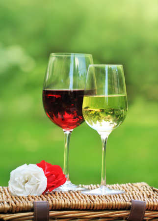 Romantic scene. Two glasses of red and white wine with roses photo