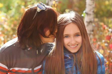 Mother and daughter teen in autumn park photo