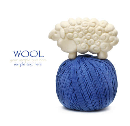 skein: Blue ball of woollen thread isolated on white with lamb figure soap on it