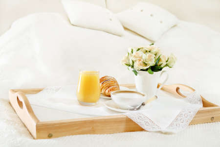 Breakfast in bed with coffee, orange juice and croissant on a tray