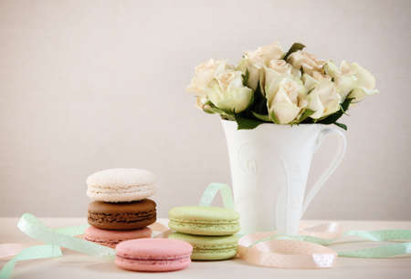 dessert stand: French macaroons on the table decorated with ribbons and roses