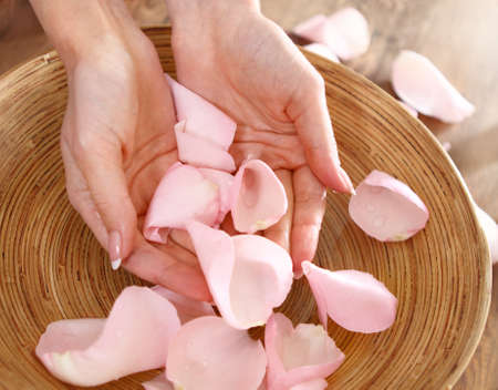 aroma bowl: Beautiful hands of the woman and rose petals. Spa or manicure concept Stock Photo