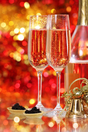 Champagne in two glasses with black caviar at the christmas background photo