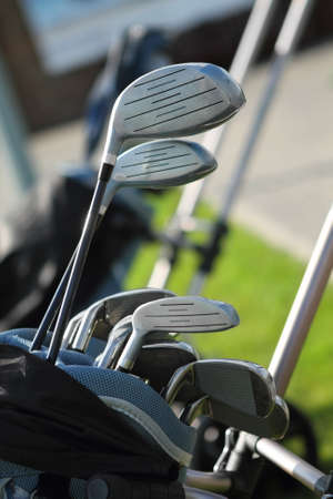 Golf clubs in golfbag, green grass background photo