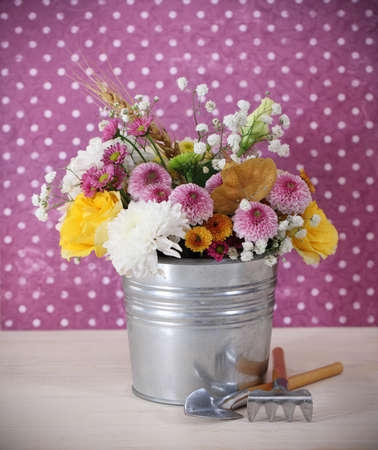 Bouquet of autumn flowers in the iron pot with garden tools photo