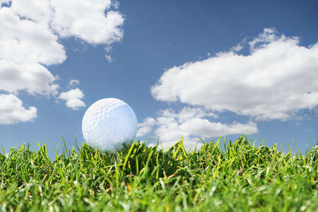 freetime activity: Close up golf course with one ball over blue sky