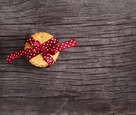 lunares rojos: Galletas decoradas con lazo rojo oscuro de lunares en el fondo de madera