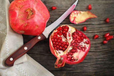 Juicy riped pomegranate  and knife on the wooden table photo