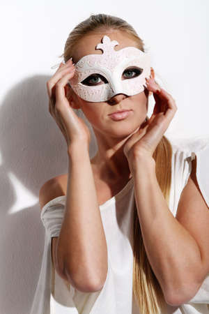 Beautiful young woman in white carnival mask photo