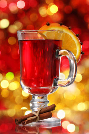 christmas drink: Orange and cranberry punch with spices over Christmas decoration
