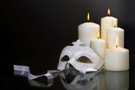 Group of candles and carnival mask over black background photo