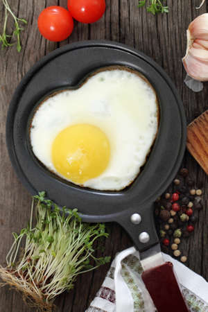 Fried egg in heart-shaped form with cress, tomato, garlic and pepper photo