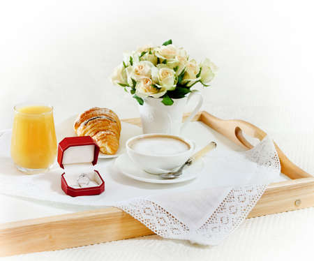 Marriage proposal. An engagement diamond ring with breakfast and bouquet of roses photo