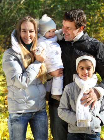 Young happy family with two daughters in autumn forest Stock Photo - 11212040