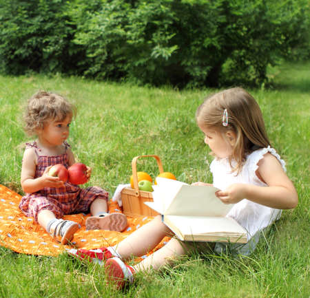 Two little sisters reading the book on picnic in summer park photo