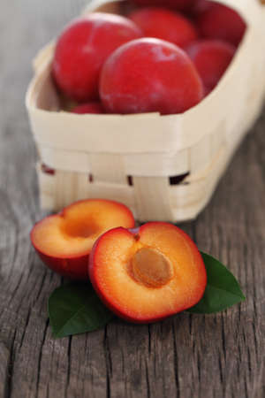 Fresh red plums and basket with them on wooden background photo