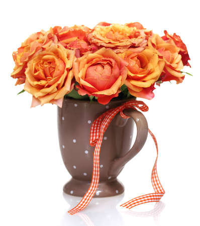 Bouquet of orange roses in the polka dots mug on the white background photo
